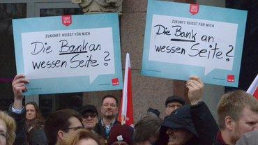 """Kollegen halten auf der Kundgebung  zwei Schilder hoch mit der Aufschrift """"Die Bank an wessen Seite?"""""""